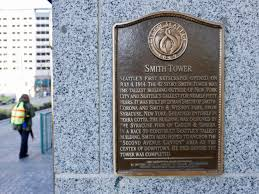 a plaque on a street level corner of smith tower in downtown seattle geekwire photo kurt schlosser