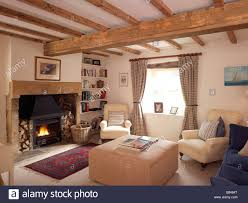 country style living room. Country Style Living Room With Lit Open Fire And Cream Furniture Gingham Curtains Wooden Beams M