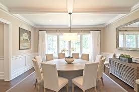 luxury dining room design with white expandable round dining table and white chairs also chandelier plus centerpiece