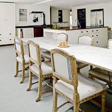 dining room flooring options uk. open-plan kitchen with neutral wood flooring, large white dining table and upholstered room flooring options uk