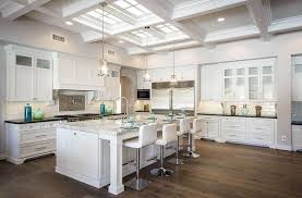open concept kitchen with white cabinets large island with marble countertops and wood flooring