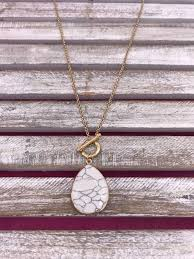 long gold necklace with white marble stone pendant
