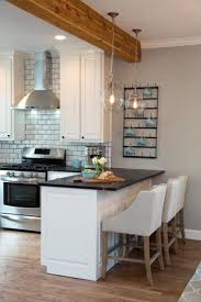 fixer upper hosts chip and joanna gaines installed a natural wood support beam above the breakfast bar a new stainless steel range and vent hood is