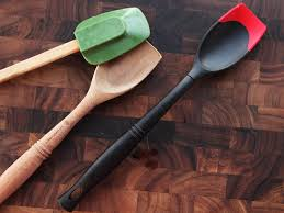 three kinds of utensils a spatula with a silicone head and wooden handle a