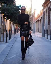 maria kragmann wears a pair of over the knee boots with a leather mini skirt and