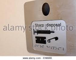 sharp disposal. sharp disposal needle bin in a public toilet england uk - stock photo