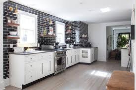 white kitchen with gray quartz countertops and glossy black backsplash tiles