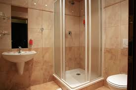 interior white floating wash basin on beige tile wall connected by small glass shower stalls