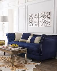 living room royal blue velvet sofa chrome coffee table tiger skin rug wooden floor white wall panel lamp throw pillows books art set sofas sectionals