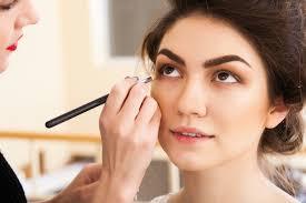 makeup artist applies eye makeup to a brunette client