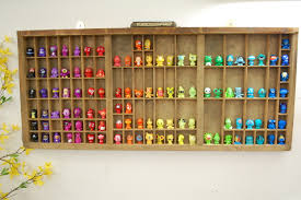 image of one of our letterpress trays hung on the wall with various toys in each