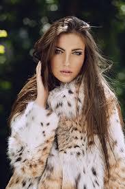 woman with brown long hair wears an animal print soft fur coat