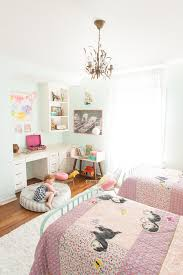 Girls room with twin beds in muted pink and mint tones with Land of Nod (