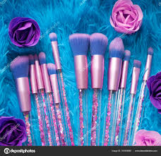 set of makeup brushes with sparkles on pink lilac and blue colored posed background