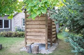 back view of a wooden outdoor shower enclosure behind a cottage