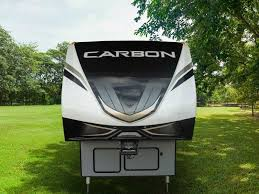 profile view of a keystone carbon toy hauler parked in a field in the shade