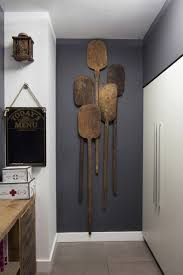 antique wooden paddles hang gray wall along several other