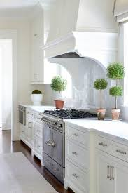 The Highlands  Sarah Bartholomew | classic white kitchen. Love the myrtle  topiaries!