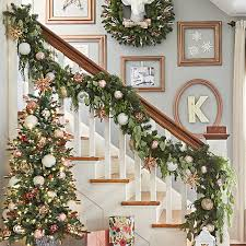 Stairway with decorated garland on banister, a lighted Christmas tree and  art on the wall
