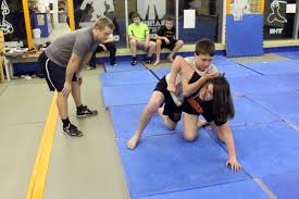 wrestling coach paul kane observes as kurt hoffman attempts a half nelson on his sister katelynne during a yorkton wrestling club practice on wednesday