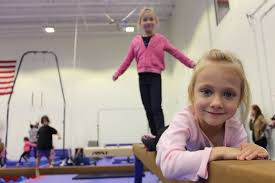 finley sabo 4 lays on a balance beam while her sister maura