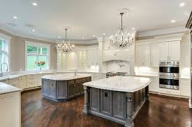 kitchen with two islands with dark contrasting cabinets and bianco carrara marble countertops