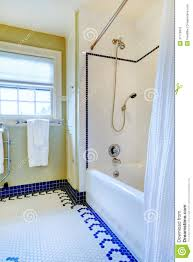 Bright Yellow And White Bathroom With Blue Tile Floor Royalty Free - Yellow and white bathroom