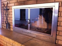 furniture stainless steel double glass fireplace doors at brick wall design above laminate wood flooring