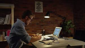 Young Concentrated Acrchitect With Light Beard And Glasses Sitting Drawing With Pencil By Computer Writing Notes With Table Lamp Stock Video Footage