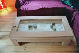 sho is a coffee table with a top glass shield protecting the highly visible zen garden scenary underneath a separate drawer is built in