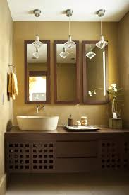 a small vanity area benefits from these mirrors the wood framed mirrors mimic the material used in the cabinet and the color complements the brown color