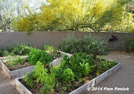 nearly a narrow gate opens onto a walled raised bed vegetable garden