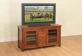 cool walnut finish wood tv stand featuring double glass door cabinets and 3 small rectangular pull out drawers