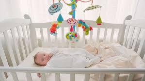 beautiful cute baby boy lying in wooden crib at big window