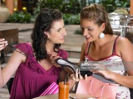 Female friends sitting with gifts at outdoor cafe stock photo