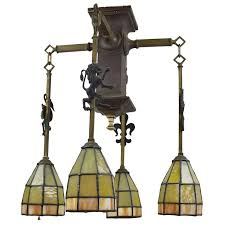 gothic arts and crafts chandelier with emblems and stained glass shades for