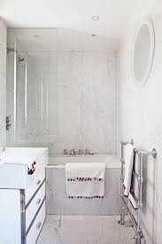 A small marble bathroom with bath shower combo. Clever ideas for small  space storage solutions