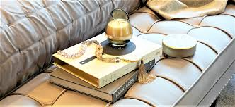 a coffee table book is a great base for grouping smaller accessories candles vases of flowers trinket trays decorative boxes or sculptural pieces