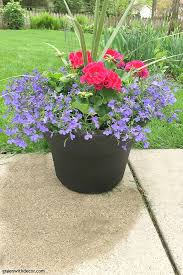 a painted plastic outdoor planter with colorful flowers