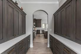 pantry fitted with facing dark brown oak shaker cabinets fitted with brass hardware and a white quartz countertop mounted under matching upper cabinets
