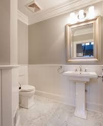 traditional powder room with complex marble tile floors crown molding wainscoting powder room