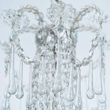 this elegant chandelier features a series of long crystal drops punctuated by crystal rosettes framing