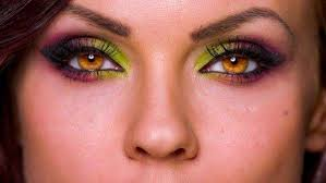 close up of beautiful female model with artistic makeup and bright amber eyes royalty