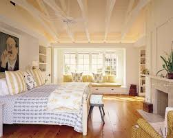 Cottage Master Bedroom with Built-in bookshelf, Exposed beam, Hardwood  floors, Window