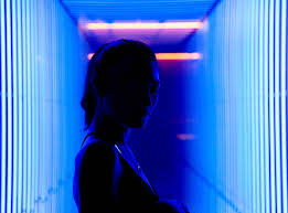 A Beautiful Woman Posing Against A Neon Blue Background