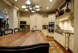 kitchen island with seating butcher block and sink under black iron chandelier