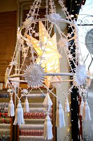 all white paper handmade pajaki in a window decorated with stars and snowflakes