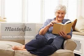 senior woman sitting on sofa reading book stock photo