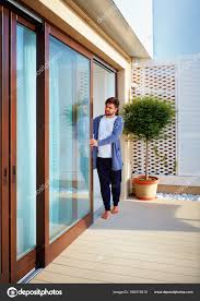 man opening sliding glass doors on patio at home stock photo