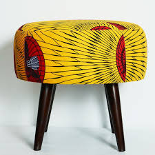 african furniture and decor. contemporary african wax print cotton ottoman with desk fan motif and overall colour of bright yellow furniture decor